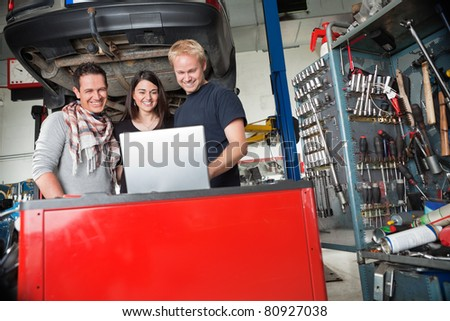 Young smiling couple standing with mechanic using laptop in auto repair shop - stock photo