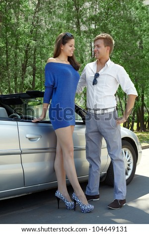 Young smiling couple stands near a cabriolet and talk about something