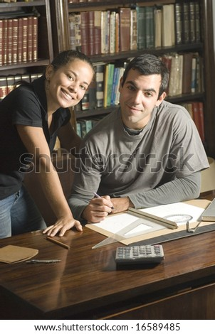 Young, smiling couple study together in an office with many books and a computer. Horizontally framed photo. - stock photo