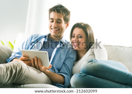 Young smiling couple with digital tablet relaxing on sofa at home