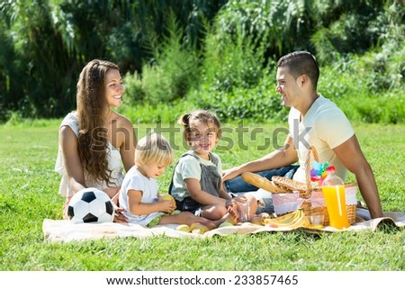 Young smiling couple with little daughters having holiday with picnic at park