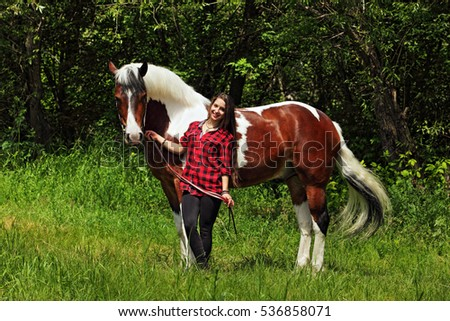 Young smiling cowgirl and horse outdoors