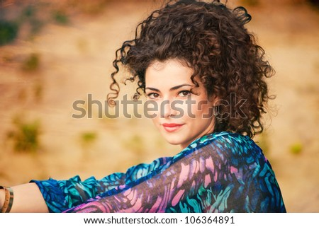 young smiling curly hair woman portrait outdoor shot summer day - stock photo