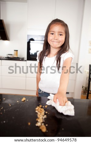 Young smiling cute girl wiping the counter after making cookies - stock photo