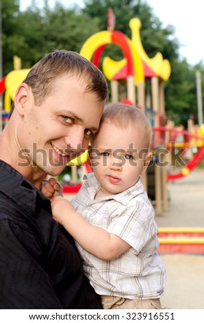 young smiling daddy holding his infant son in hands on playground outdoors - stock photo
