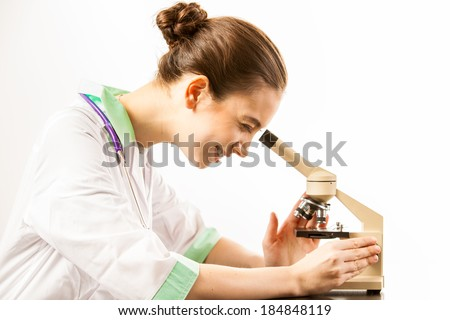 Young smiling doctor looking into a microscope
