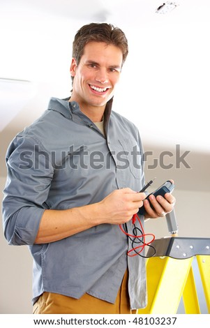 Young smiling electrician doing his work - stock photo