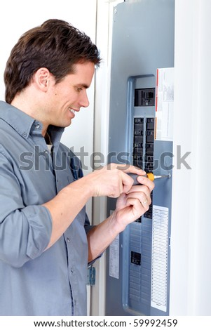 Young smiling electrician doing his work