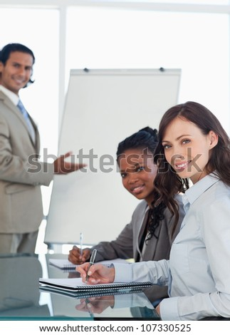 Young smiling employees working during a presentation and writing in a notebook