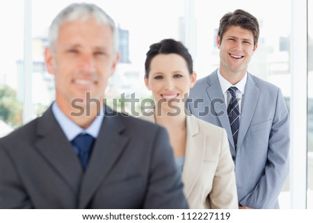 Young smiling executive standing behind two business people