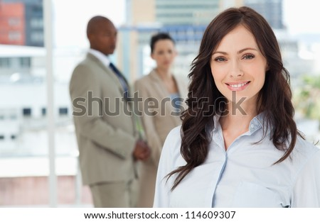 Young smiling executive standing in front of her business team