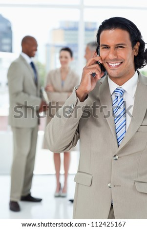 Young smiling executive talking on the phone and with his team behind him