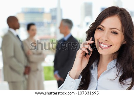 Young smiling executive woman on the cell phone and tilting her head to one side - stock photo