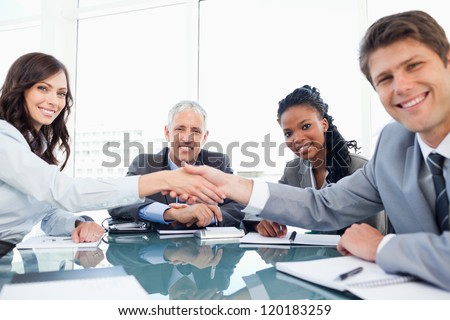 Young smiling executives shaking hands while looking at the camera - stock photo