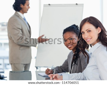 Young smiling executives working while listening to a presentation - stock photo