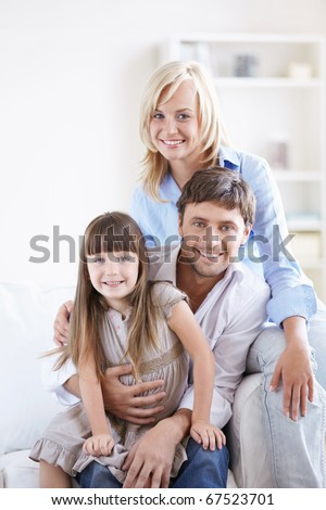 Young smiling family with a child at home - stock photo