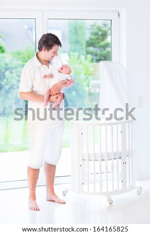 Young smiling father holding his newborn baby standing next to a white round crib with canopy at a big window - stock photo