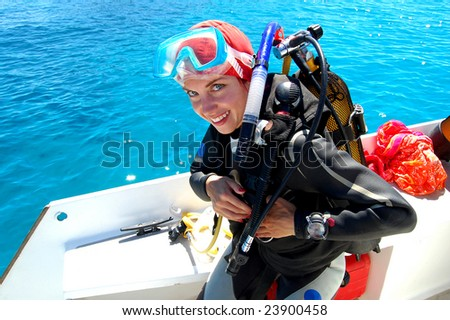 Young smiling female diver preparing for the dive - stock photo
