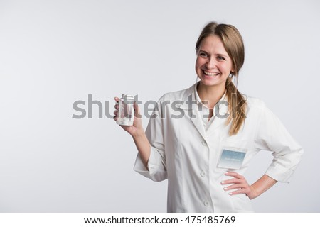 Young smiling female doctor presenting a white unlabeled bottle or recipient of pills
