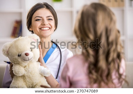 Young smiling female doctor with teddy bear and little girl. - stock photo