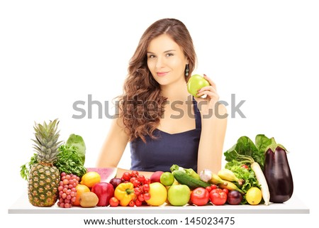 Young smiling female holding a green apple and posing behind a table full of vegatebles and fruits isolated on white background - stock photo