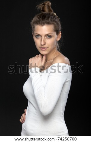 Young smiling female holding her hands near the face isolated on black - stock photo