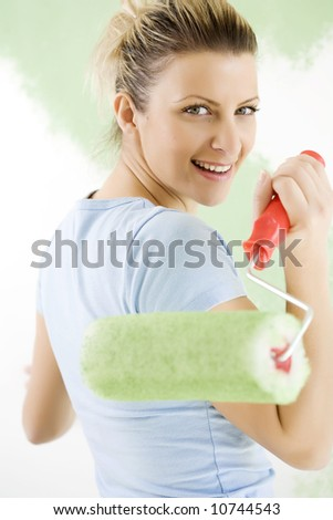 young smiling female painting her house