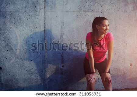 Young smiling female resting after an active fitness training while standing against gray wall with copy space area for your text message, satisfied fit woman resting after an active fitness training - stock photo