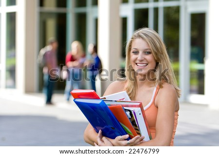 Young smiling female student carrying her books outside of school.  There are kids in the background. Horizontally framed photo. - stock photo