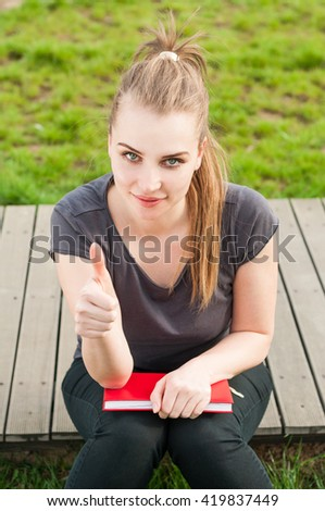 Young smiling female with book in the park show thumbup or like gesture enjoying summer day