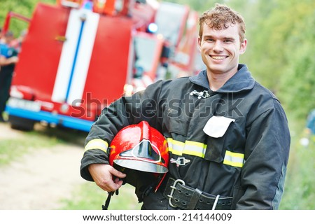 young smiling fireman firefighter in uniform in front of fire engine machine - stock photo