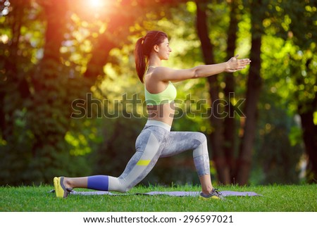 Young smiling fitness woman doing fitness exercises in the park on green grass. Fitness training outdoors. Fitness classes outdoors. Attractive fitness woman. Workout outdoors. Healthy lifestyle - stock photo