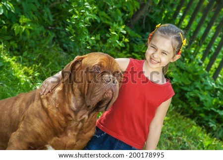Young smiling girl astride big dog of breed FRENCH MASTIFF, DOGUE DE BORDEAUX - stock photo