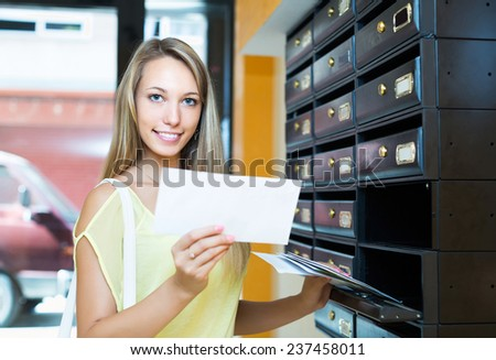 Young smiling girl checking up letter-box indoor - stock photo