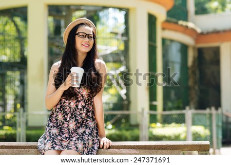 Young smiling girl drinking coffee in the park - stock photo
