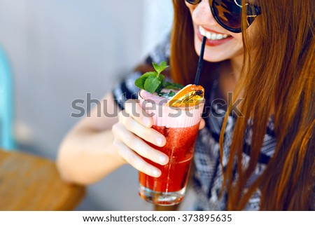 Young smiling girl drinking tasty sweet cocktail , amazing relaxing day, tasty lemonade, elegant dress and sunglasses, outdoor terrace.
