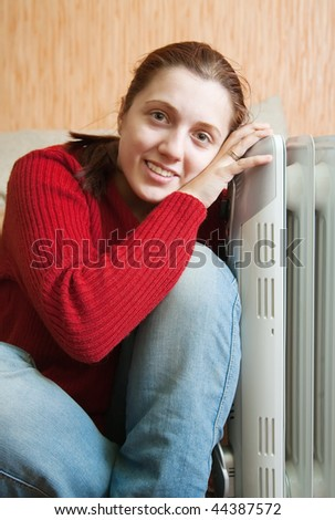 young smiling girl is sitting near oil heater - stock photo