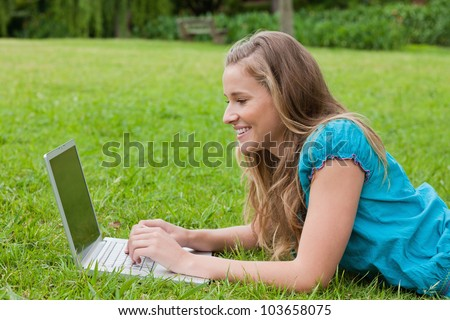 Young smiling girl looking at her laptop while lying on the grass in the countryside - stock photo