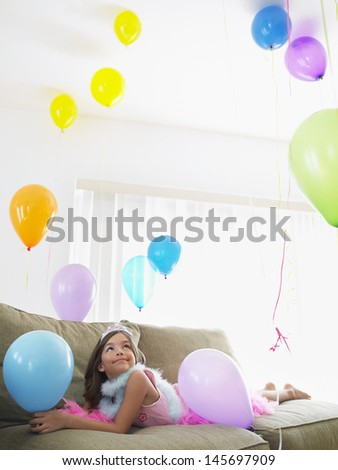 Young smiling girl lying on sofa and looking up at balloons