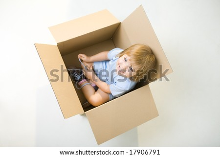 Young smiling girl sitting in cardboard box. She's looking at camera. High angle view. - stock photo