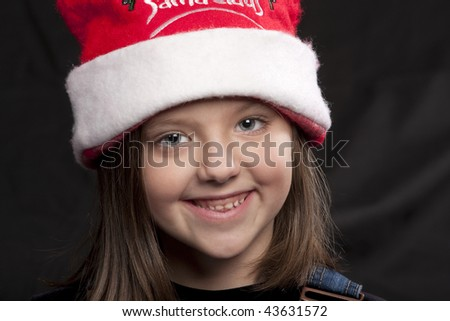 Young smiling girl wearing a red and white Santa Claus hat for Christmas - stock photo
