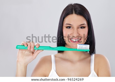 Young smiling girl with healthy teeth holding big toothbrush - stock photo