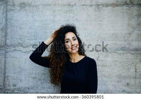 Young smiling girl with long curly hair while standing against gray concrete wall with copy space area for your text message - stock photo