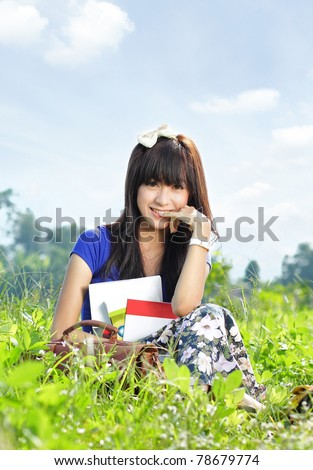 Young smiling girl with many books