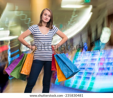 Young smiling girl with shopping bags at shopping mall