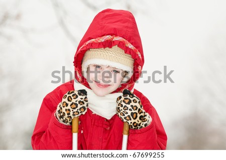 Young smiling girl with skiing sticks in warm clothing at white winter forest outdoors