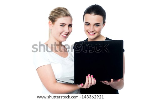 Young smiling girls holding laptop