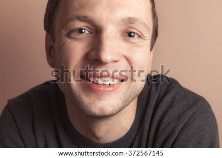 Young smiling handsome Caucasian man, closeup studio portrait over gray wall background - stock photo