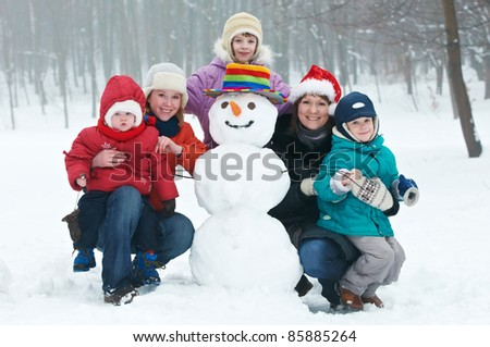 young smiling happy woman with children and snowman with color hat at winter outdoors - stock photo