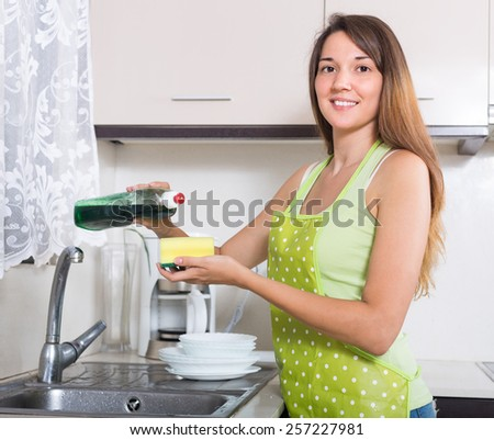 Young smiling housewife washing plates with sponge in domestic kitchen  - stock photo